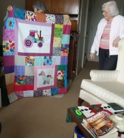 Laurie is hiding behind her quilt that she made for a friends child. Dolly admires it.