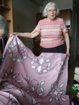 Dolly shows her quilt top that she will hand quilt.